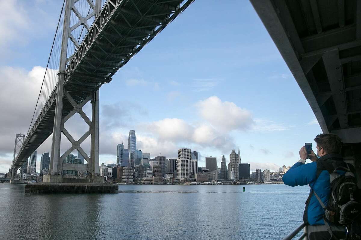 A passenger takes a photo of the San Francisco skyline while crossing under the Bay Bridge on the Oakland-Alameda to San Francisco Ferry in San Francisco, California on Nov. 23, 2020.