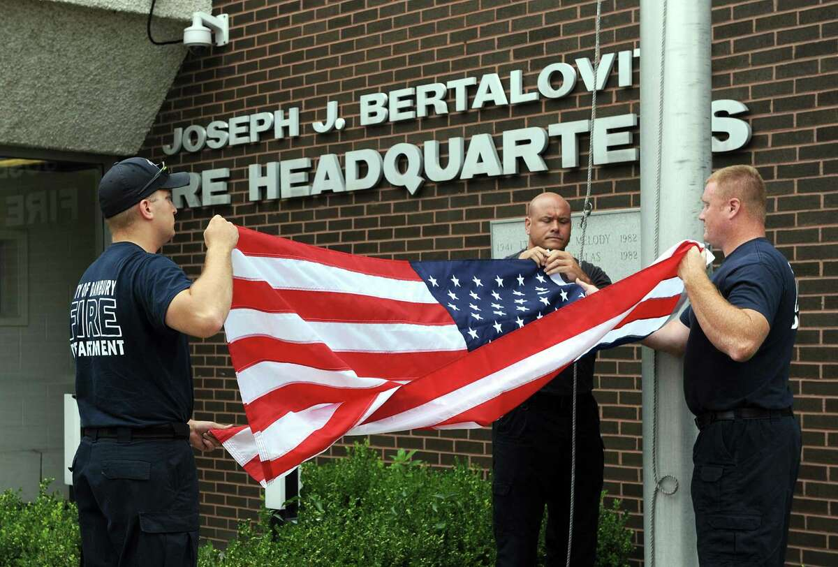 From left, Firefighters Scott Yaglowski, Jason Culbreth and Adam Horosky lower and fold an American flag that flew of the Danbury Fire Department at the New Street headquarters, Tuesday, July 25, 2017. This is part of a flag ceremony held for Lt. Albert Mion who is retiring just shy of 34 years of service.