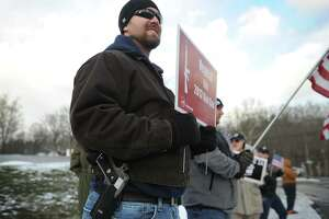 Robert Harris, of Old Saybrook, open carries as he and fellow gun rights advocates oppose a gun control rally outside the National Shooting Sports Foundation's headquarters in Newtown, Conn. on Monday, January 18, 2016.