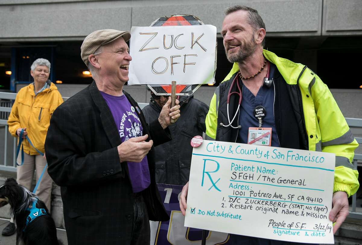 """Retired hospital employee Mike Dingle (left) carries a sign that reads """"Zuck Off"""" while greeting Guy Vandenberg, a nurse who was suspended recently for speaking out about removing Mark Zuckerberg's name from the hospital, while protesting outside of Zuckerberg San Francisco General Hospital in San Francisco, Calif. Friday, March 22, 2019."""