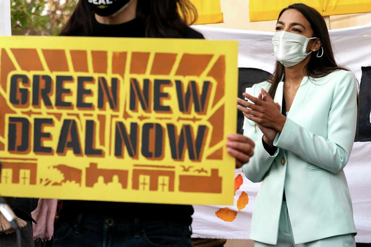 Rep. Alexandria Ocasio-Cortez, D-N.Y., claps along during a song by climate activists, Thursday, Nov. 19, 2020, outside the Democratic National Committee (DNC) Headquarters in Washington.