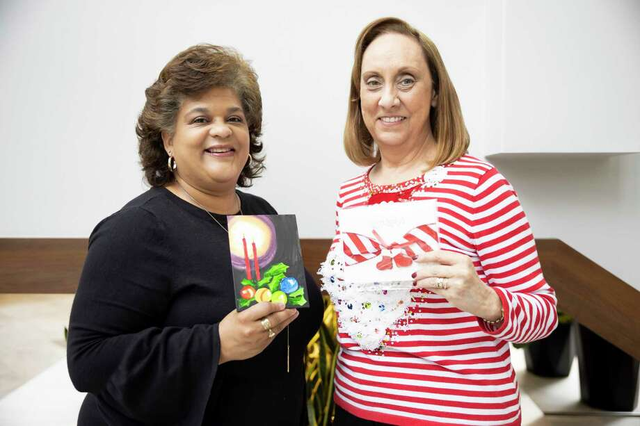 Enid Goodman, left and Sheri Brown, right, both with Bridgewood Farms pose for a portrait with artwork made by their clients during a grant check distribution at the Community Foundation of Montgomery County, Thursday, Dec. 3, 2020. Bridgewood Farms received $6,800 from the Community Foundation to purchase equipment for their gym, to support nutrition and exercise programs for their clients. Photo: Gustavo Huerta, Houston Chronicle / Staff Photographer / 2020 © Houston Chronicle