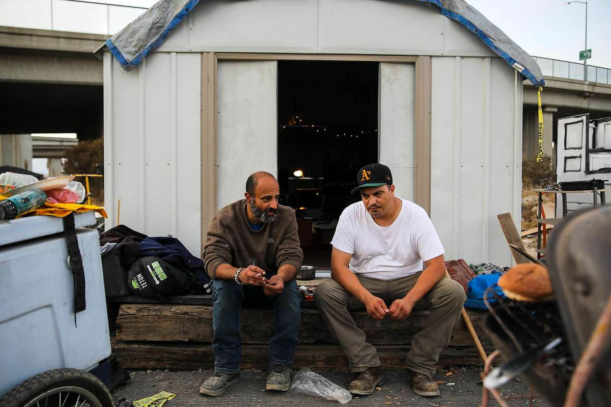 Old friends Moose Saberi, 44 (left), and Gabriel Cano, 42, chat at Saberi's shed in a homeless camp.