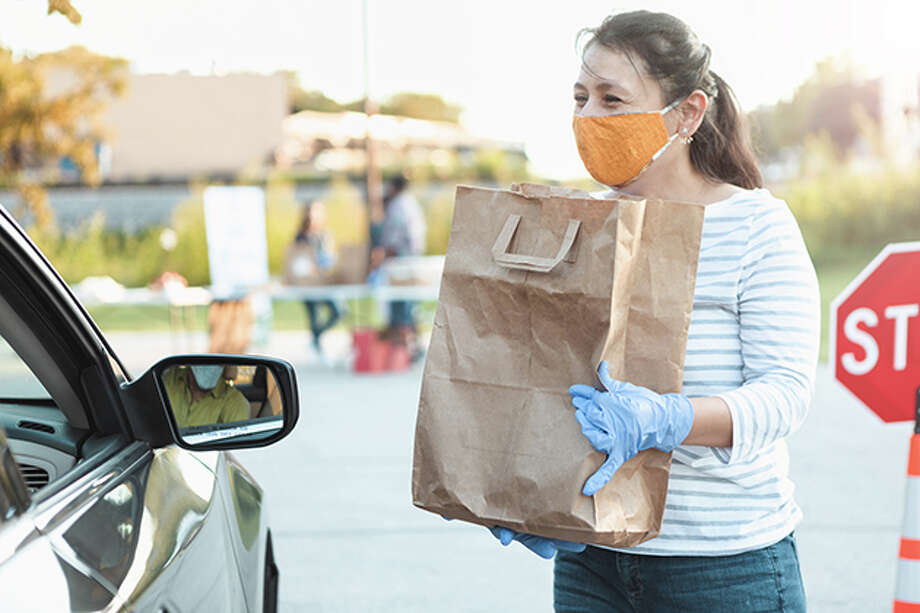 A female volunteer prepares to bag of food to someone in a car during a drive through food drive. Photo: Getty Images