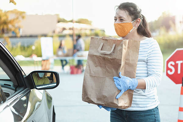A female volunteer prepares to bag of food to someone in a car during a drive through food drive.