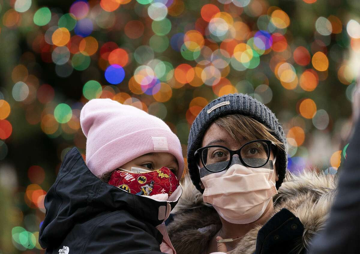 A woman holds her daughter as they pose for photos at the Rockefeller Center Christmas Tree, Thursday, Dec. 3, 2020 in New York. What's normally a chaotic, crowded tourist hotspot during the holiday season is instead a mask-mandated, time-limited, socially distanced locale due to the coronavirus pandemic. (AP Photo/Mark Lennihan)