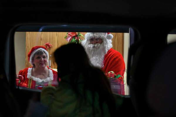 Mr. and Mrs. Claus talk to students during FirstCapital Bank of Texas' drive-thru Christmas events for students at Bonham Elementary School on Thursday, Dec. 3, 2020 at 5606 West Wadley Avenue. Jacy Lewis/Reporter-Telegram
