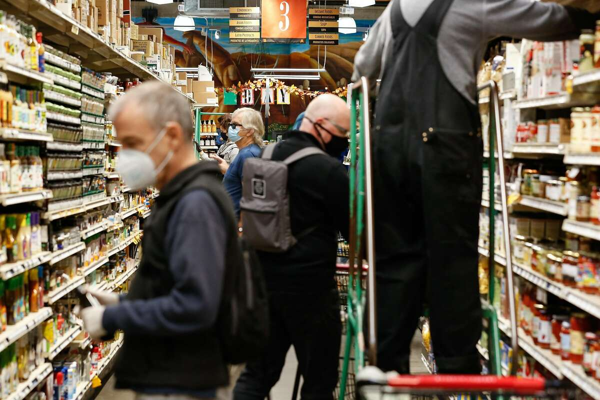 Shoppers look for items in Rainbow Grocery in November. Stores like Rainbow have added more suppliers since panic buying emptied some shelves early in the pandemic.