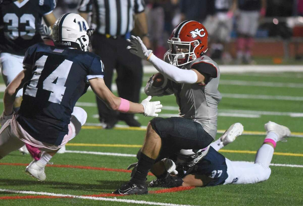 New Canaan's Zach LaPolice (7) evades Staples' Ryan Thompson (14) and Guy Harizman (37) during a football game in Westport on Friday, Oct. 25, 2019.