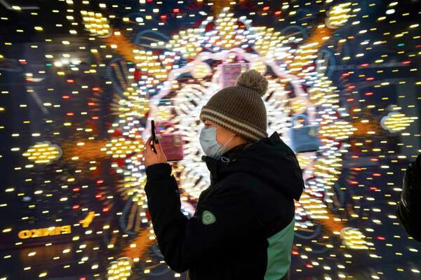A visiter wearing a face mask looks at her smartphone as she walks in the GUM State Department store decorated for Christmas and New Year celebrations virtually empty due to the coronavirus pandemic in Moscow, Russia, Thursday, Dec. 3.
