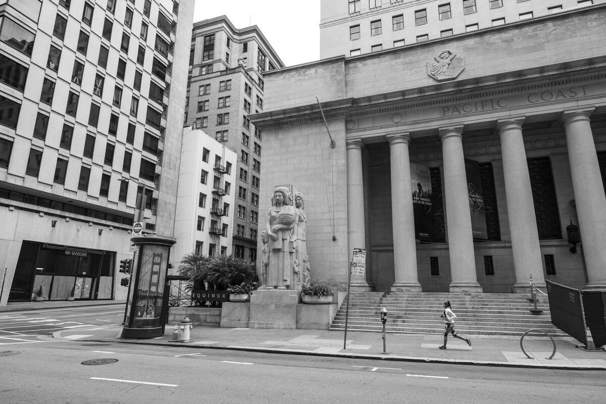 In this photo taken Friday, April 17, 2020, a woman jogs past the former Pacific Stock Exchange building in the Financial District of San Francisco. Normally, the months leading into summer bring bustling crowds to the city's famous landmarks, but this year, because of the coronavirus threat they sit empty and quiet. Some parts are like eerie ghost towns or stark scenes from a science-fiction movie.