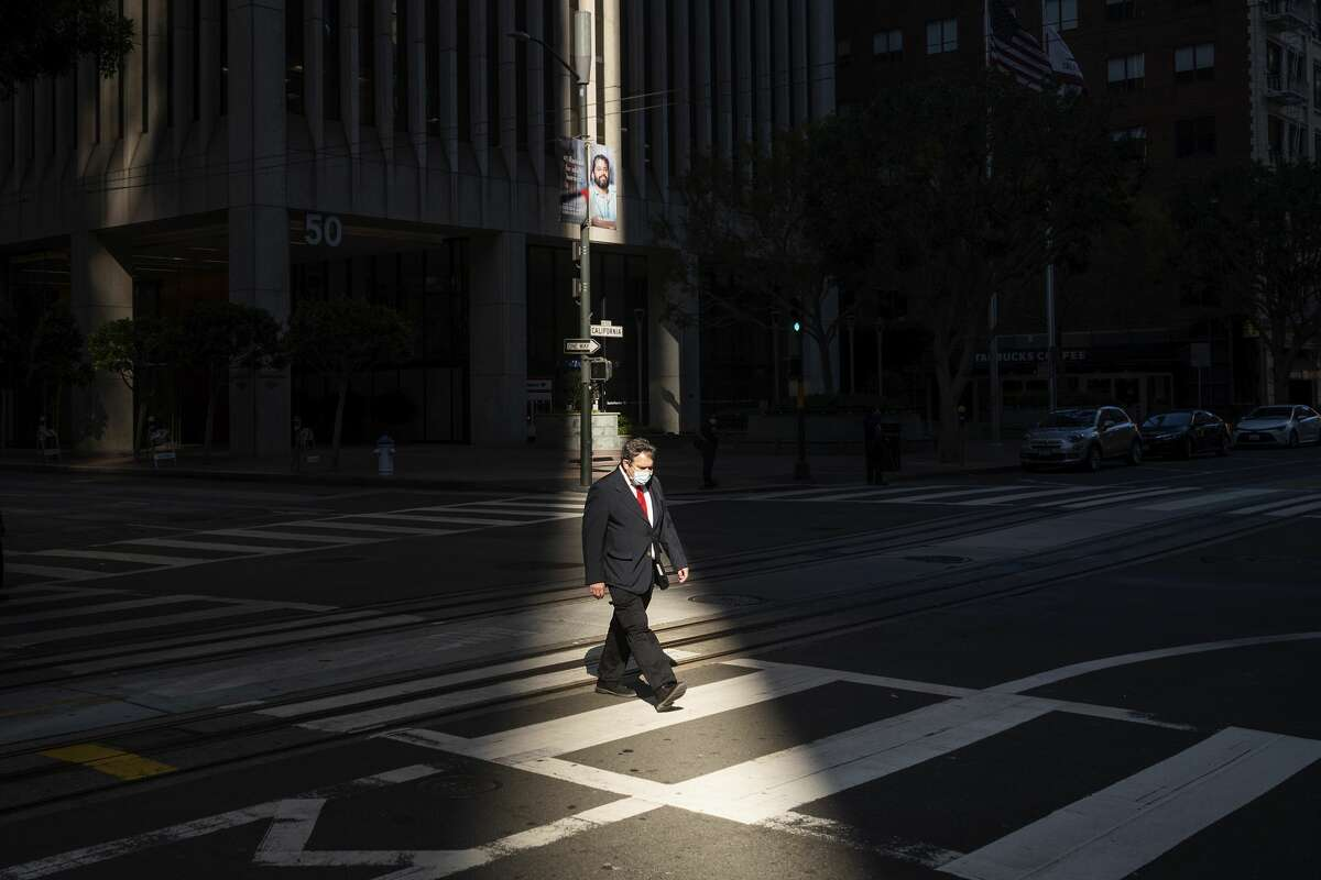 A worker crosses an intersection in San Francisco's financial district mid-afternoon, during what would've been a bustling time before the COVID-19 pandemic, on Wednesday, Oct. 21, 2020. The area remains largely devoid of activity as many employees continue to work from home.