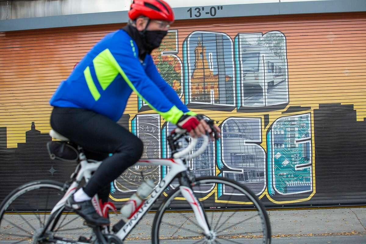 A masked biker rolls past a mural in downtown San Jose, CA on December 3, 2020.