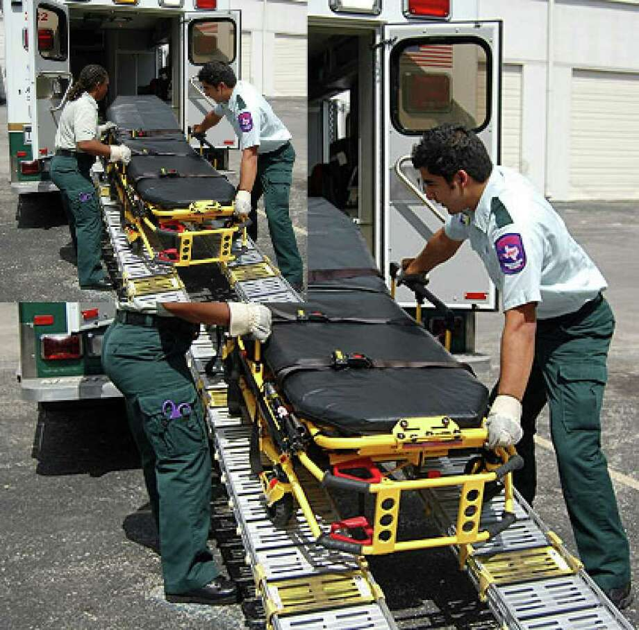 "EMTs Pam Moore and Jason Martinez roll a special stretcher up a ramp into a ""bariatric ambulance"" operated by Acadian Ambulance Service that is designed to transport obese patients."