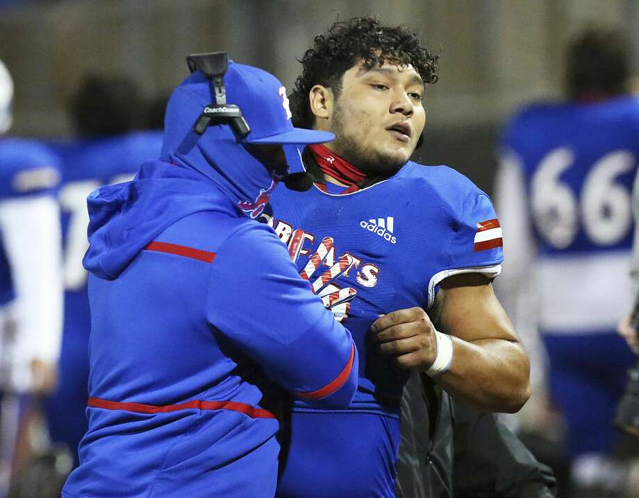Edinburg's Emmanuel Duron is pulled from the field by coaching staff after charging a referee during a high school football zone play-in game against Pharr-San Juan-Alamo on Thursday, Dec. 3, 2020, in Edinburg, Texas. Duron came running from the sideline area after the referee announced his ejection, slamming into the official. Duron was escorted from the stadium by police. (Joel Martinez/The Monitor via AP) Photo: Joel Martinez/Associated Press / The Monitor