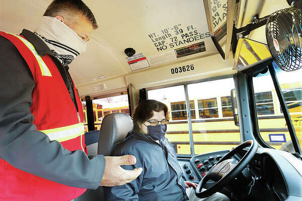 Telegraph reporter Dylan Suttles, right, sits behind the wheel of a full-size Illinois Central School Bus rig as he gets a lesson in how to operate the bus from Mark Walsh, the Human Resources Recruiting Manager for Illinois Central's parent company. Illinois Central operates busses in the Alton School District.