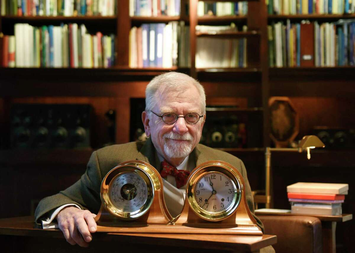 Bill Baker poses with clocks from his collection in his home in the Riverside section of Greenwich. Baker was president of WNET/Channel 13 for more than 20 years.