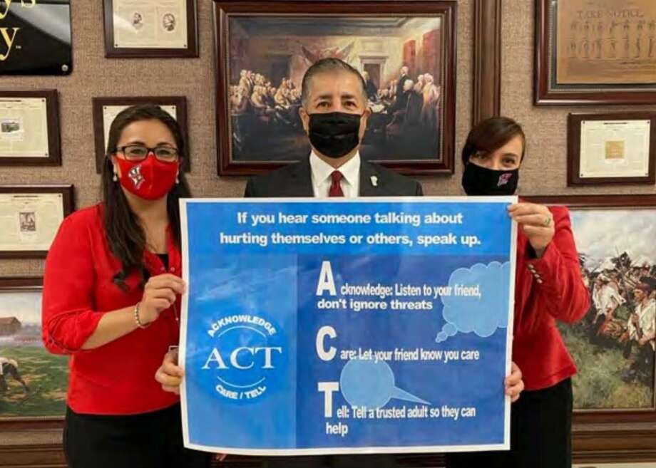 David Gonzalez and UISD counselors Maria Guajardo and Rosa Gutierrez share a poster encouraging students to ACT. Photo: Courtesy /Texas School Business