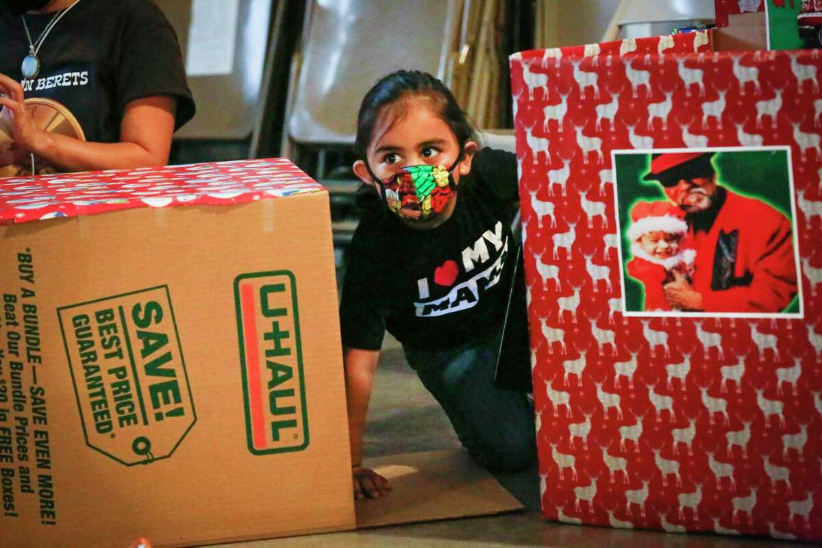 Eli Itzli Rodriguez, 3, keeps an eye on her mother, Gabriella A. Rodriguez wrapping a donation box as volunteers came to the aid of Pancho Claus aka Richard Reyes who for the first time is asking for help to continue the holiday tradition of spreading joy to underprivileged children Saturday, Nov. 14, 2020, in Houston.