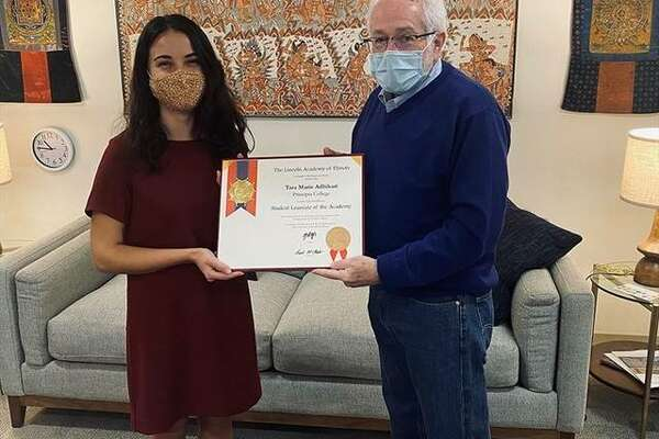 Principia College President John Williams, right, presents the Abraham Lincoln Civic Engagement Award certificate to senior Tara Adhikari. The award recognizes her eadership and service in the pursuit of the betterment of humanity and overall excellence in curricular and extracurricular activities.