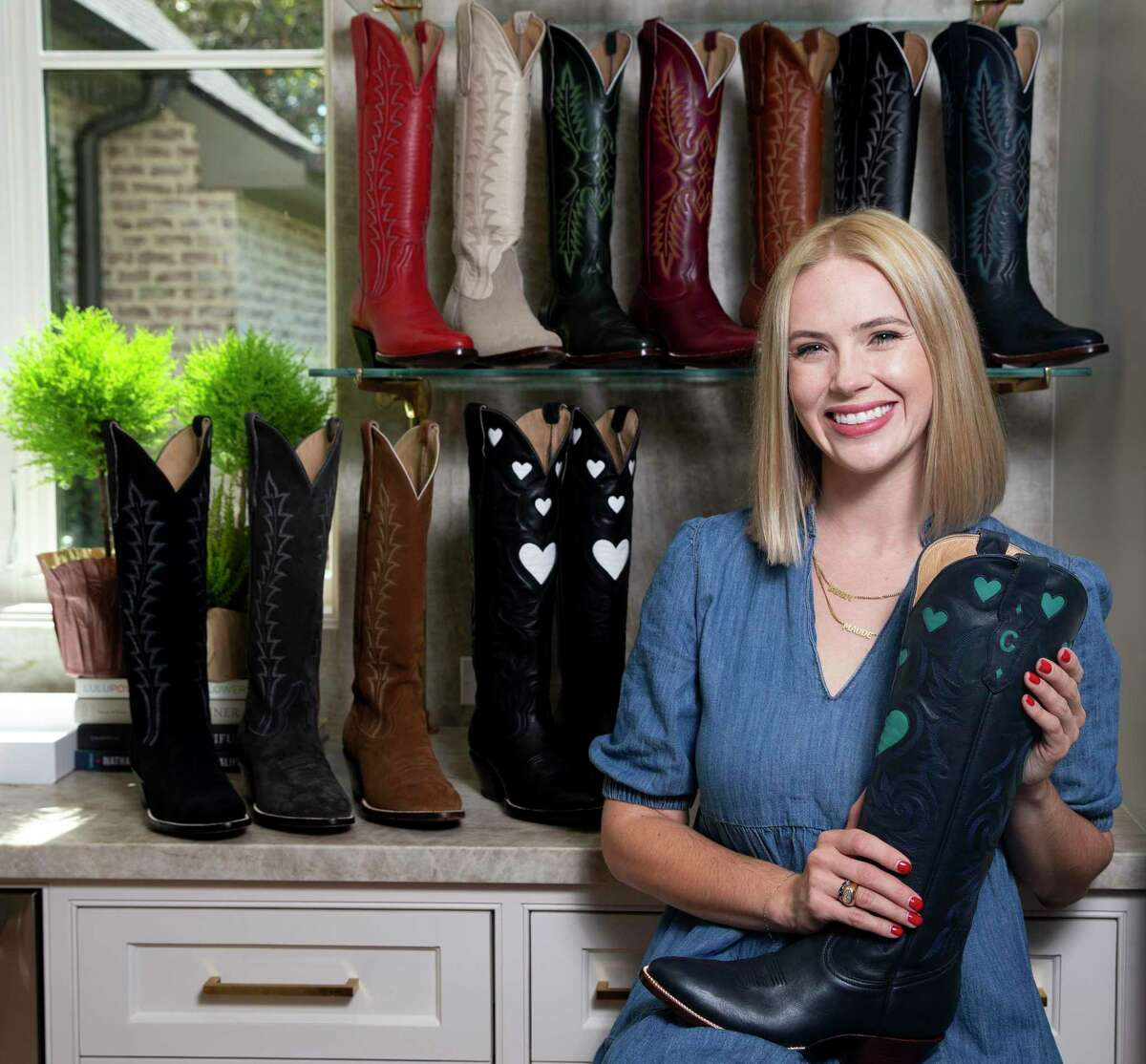 Lizzy Chesnut Bentley, founder of CITY Boots, poses for a photograph with the brand's boots collection Friday, Oct. 2, 2020, in Houston.