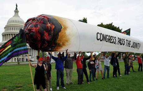 Activists from the DC Marijuana Justice (DCJM) hold a giant marijuana joint to demand Congress to pass cannabis reform legislation on the East Lawn of the US Capitol in Washington, DC on October 8, 2019. (Olivier Douliery/AFP via Getty Images/TNS)