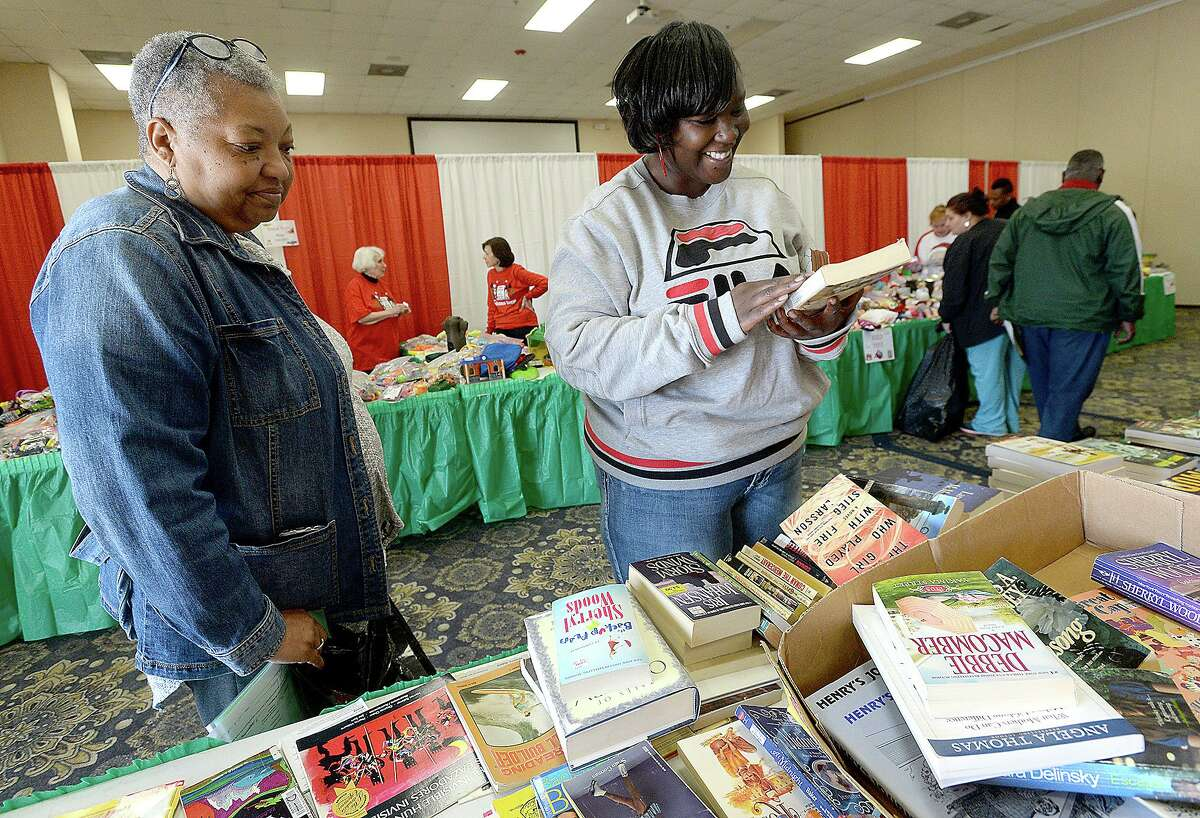 Volunteer Emilie West helps Marian Harris find books for her children and one for herself while she shops for her gifts at the annual distribution of the EJ Empty Stocking Fund gifts to families in need at the Compro Event Center. Photo taken Wednesday, December 5, 2018 Kim Brent/The Enterprise