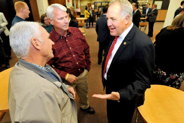 U.S. Congressman John Shimkus, right, talks with Steve Barker, left, and Randy Shroyer at the Lovejoy Library at SIUE before a presentation last year.