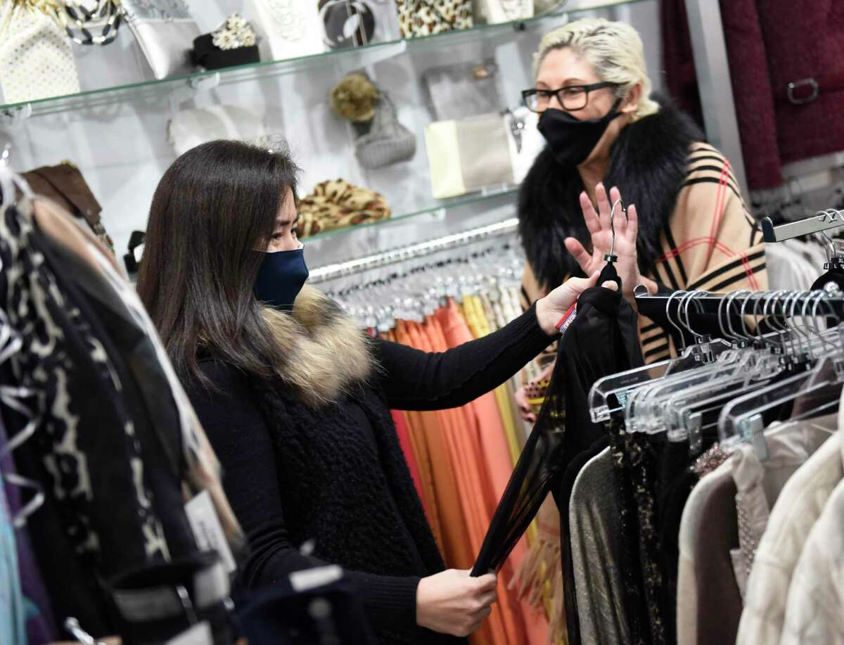 An associate helps a customer shop during the Toys for Tots holiday fundraiser at Helen Ainson in Darien, Conn. Tuesday, Dec. 1, 2020. The boutique clothing shop usually holds a fashion show for its annual Toys for Tots fundraiser, but opted for a more intimate and scaled-down version of the event this year.