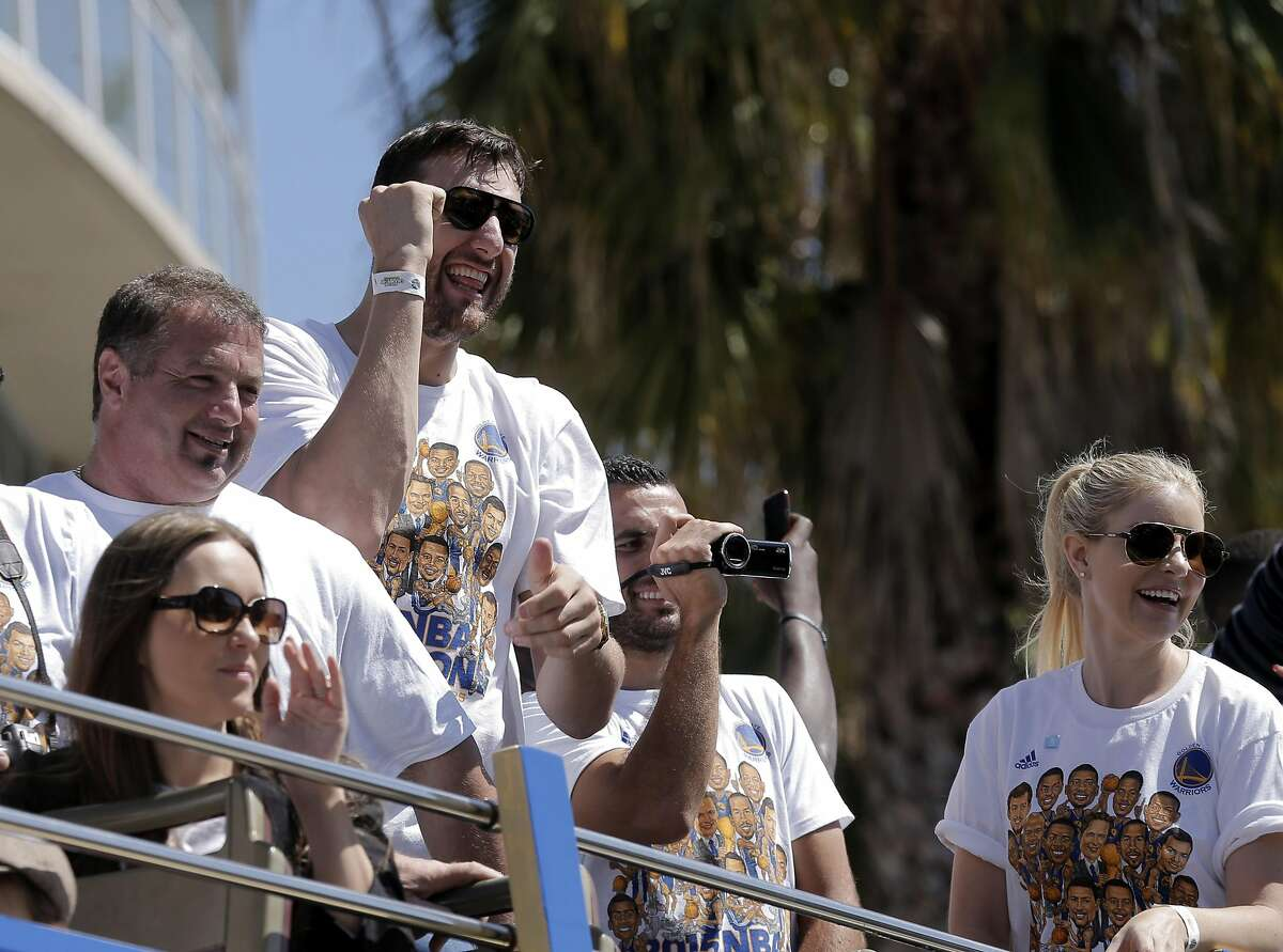 Warriors center Andre Bogut acknowledges the crowd on Lakeside Drive as the Warriors victory parade passes by on Friday. The Golden State Warriors celebrated their first NBA Championship in 40 years with a parade through Oakland, Calif., on Friday, June 19, 2015.