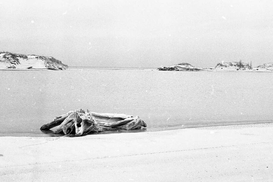 """In the News Advocate 40 years ago today,Man Made Lake made front page news when it was made known that a 50-yard wide sand barrier between Lake Michigan and Man Made Lake had broken and enlarged over consecutive days. This photo was taken from the east side of Man Made Lake showing Lake Michigan in the background.""""(Manistee County Historical Museum photo)"""