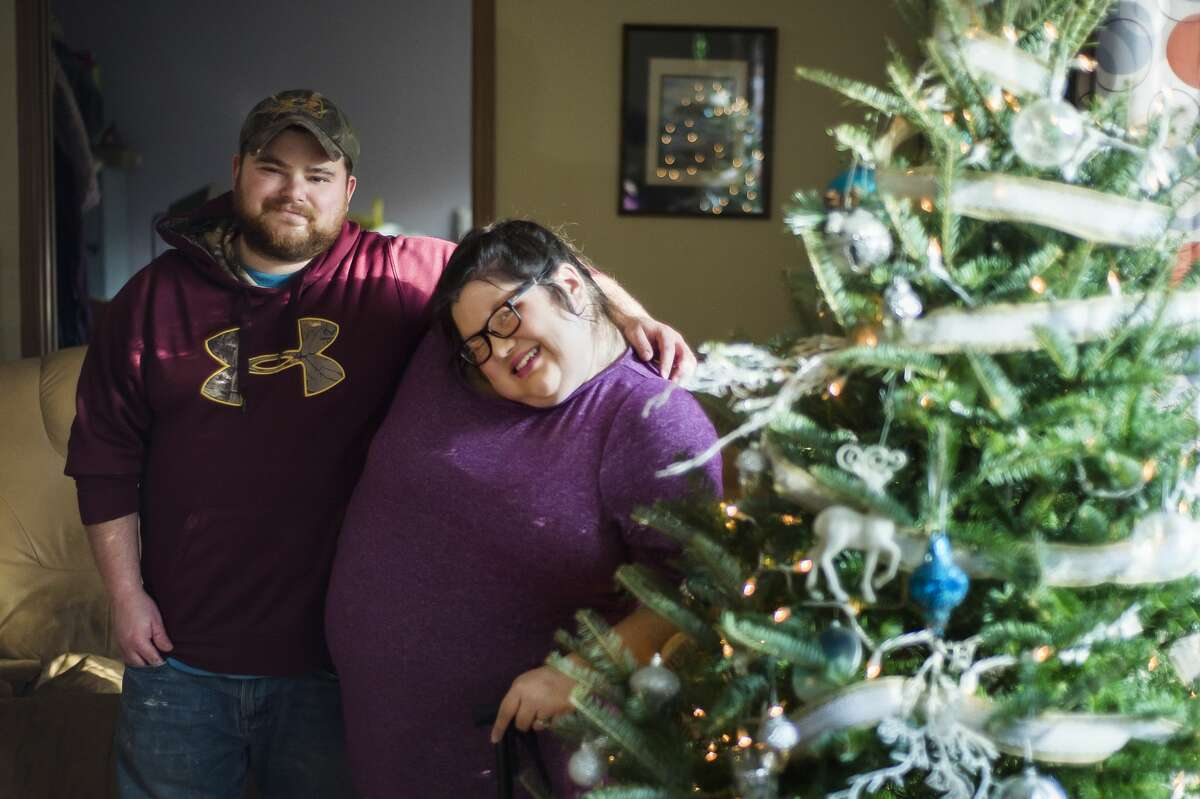 Aaron Zeiler, left, and his wife Sabrina Zeiler, right, pose for a portrait next to the Christmas tree Friday, Dec. 4, 2020 at their home in Shepherd. (Katy Kildee/kkildee@mdn.net)