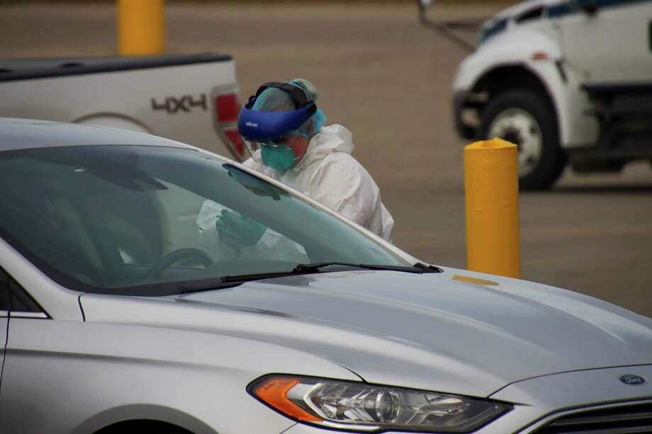 A healthcare worker starts to open the nasal swab packaging during a drive-thru testing day in Bad Axe late November. (Scott Nunn/Tribune File Photo)