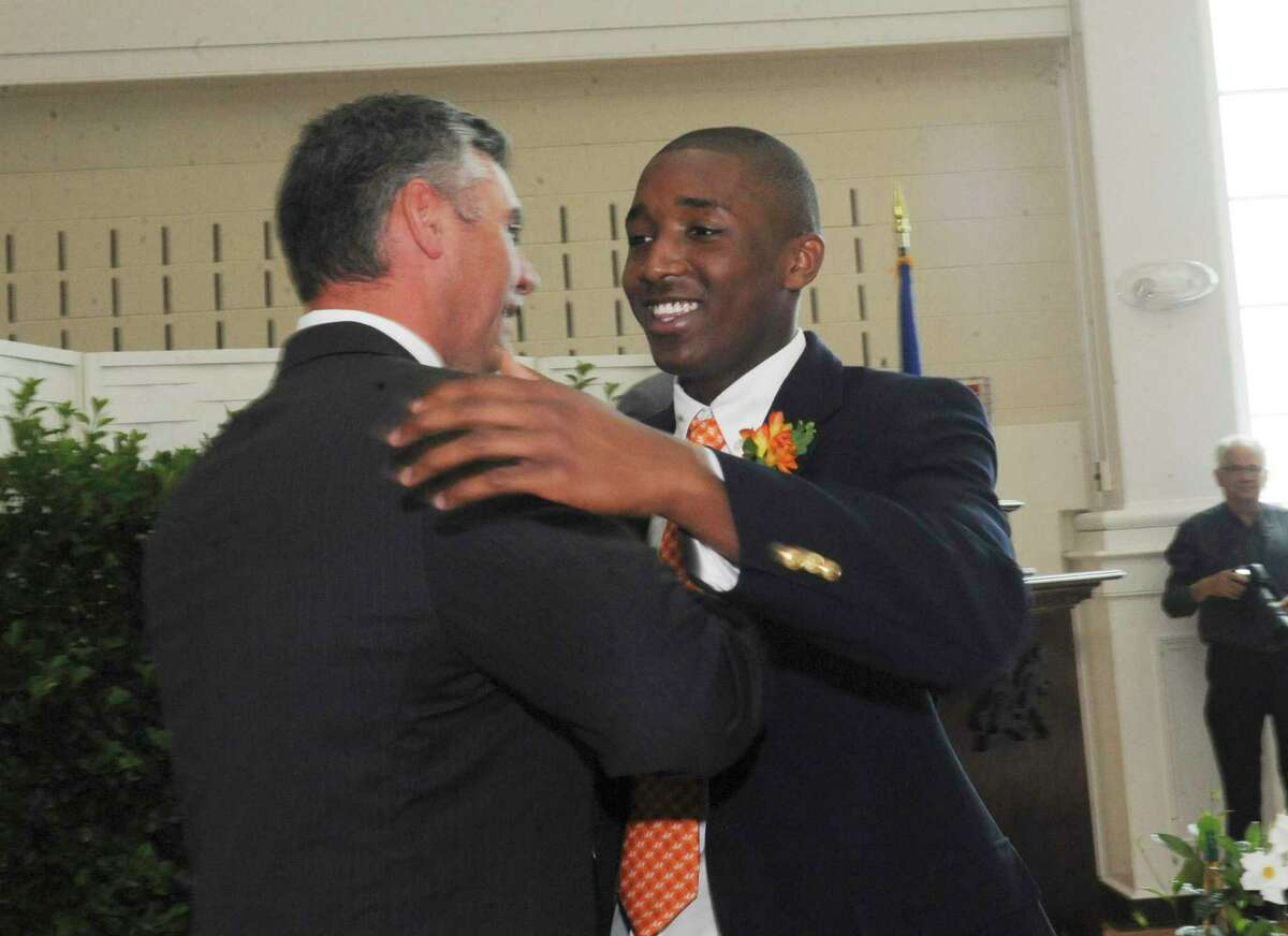 After he was honored for graduating, Donovan V. Mitchell Jr. hugs Headmaster Adam C. Rohdie during Greenwich Country Day School's 85th commencement Thursday, June 14, 2012.