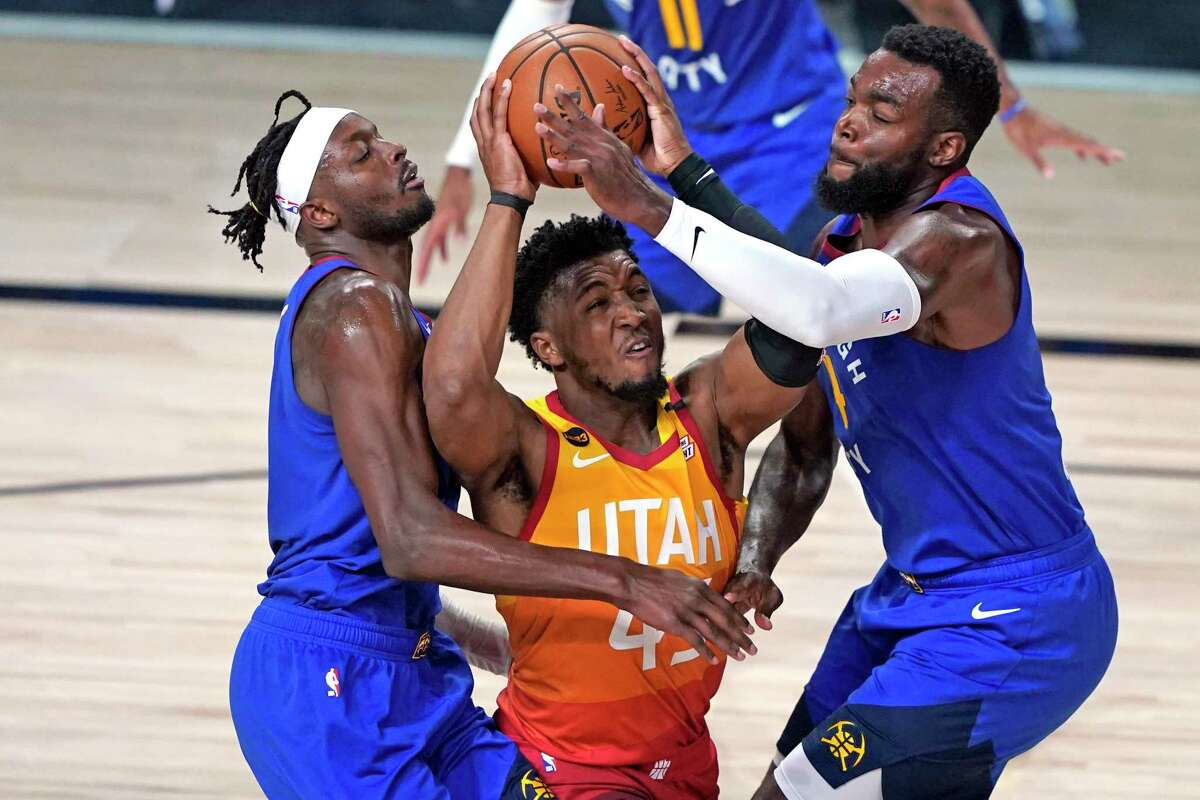 In this Aug. 30, 2020, file photo, Utah Jazz's Donovan Mitchell, center, goes up to shoot as Denver Nuggets' Jerami Grant, left, and Paul Millsap, right, defend during the second half of an NBA basketball first round playoff game in Lake Buena Vista, Fla. Mitchell agreed Sunday, Nov. 22, 2020, to a five-year, $163 million extension to remain with the Jazz. (AP Photo/Ashley Landis, File)