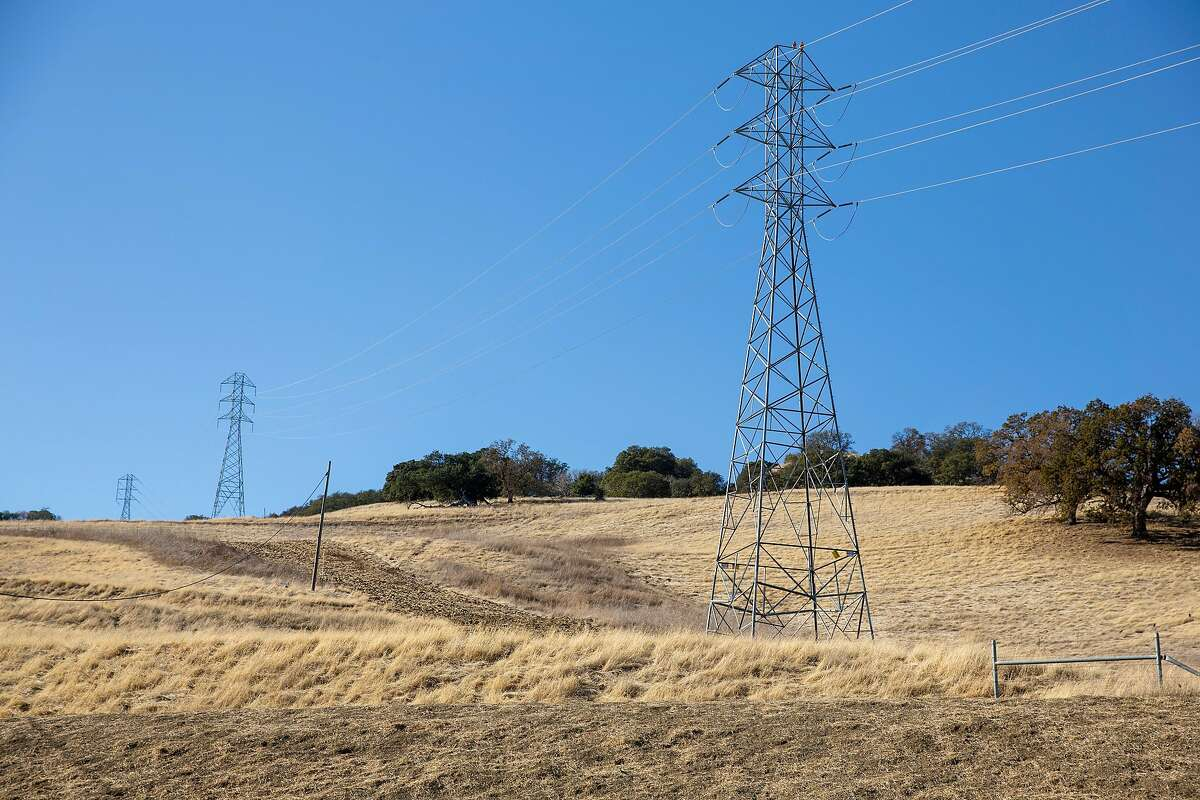 Dry grass surrounds power lines in Concord, Calif. on Friday, December 4, 2020.