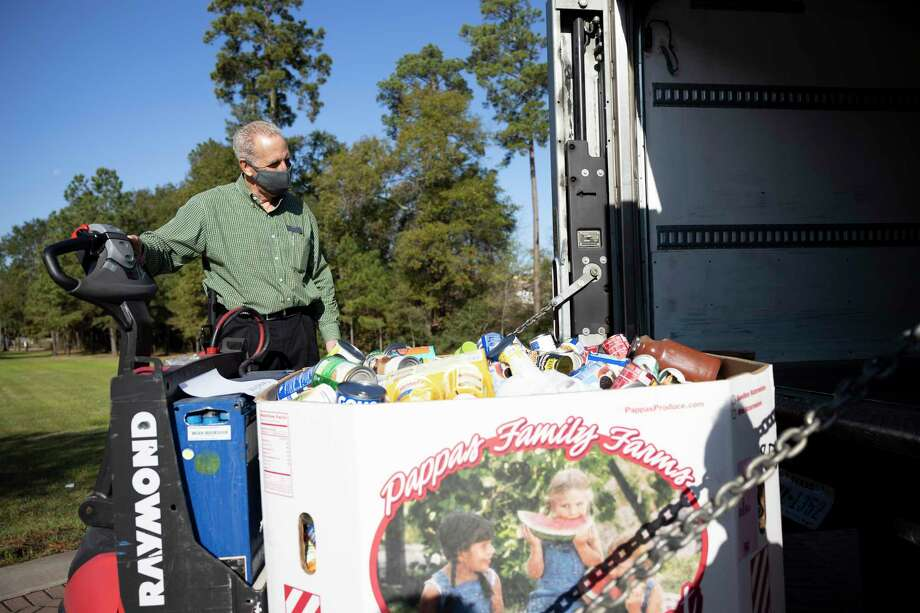 John Kreger, COO of the Montgomery County Food Bank, loads a pallet of food onto a trailer during a holiday food drive held at the Woodlands United Methodist Church, Friday, Dec. 4, 2020. Entertainment was provided by local schools to offer holiday cheer for volunteers and donors. Photo: Gustavo Huerta, Houston Chronicle / Staff Photographer / 2020 © Houston Chronicle