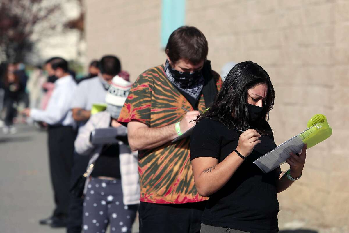 Karina Carillo of San Jose fills out a registration form as she stands in line with others for a COVID-19 test at Emmanuel Baptist Church on Friday, December 4, 2020 in San Jose, Calif.