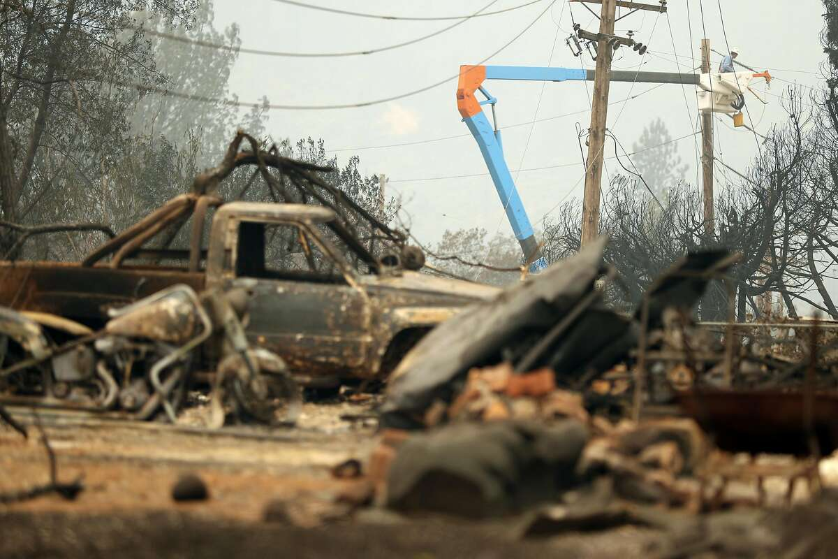 PG&E technicians work on restoring power after the Carr Fire in Shasta County in July 2018. The utility company has won approval for a rate increase after disastrous wildfires.