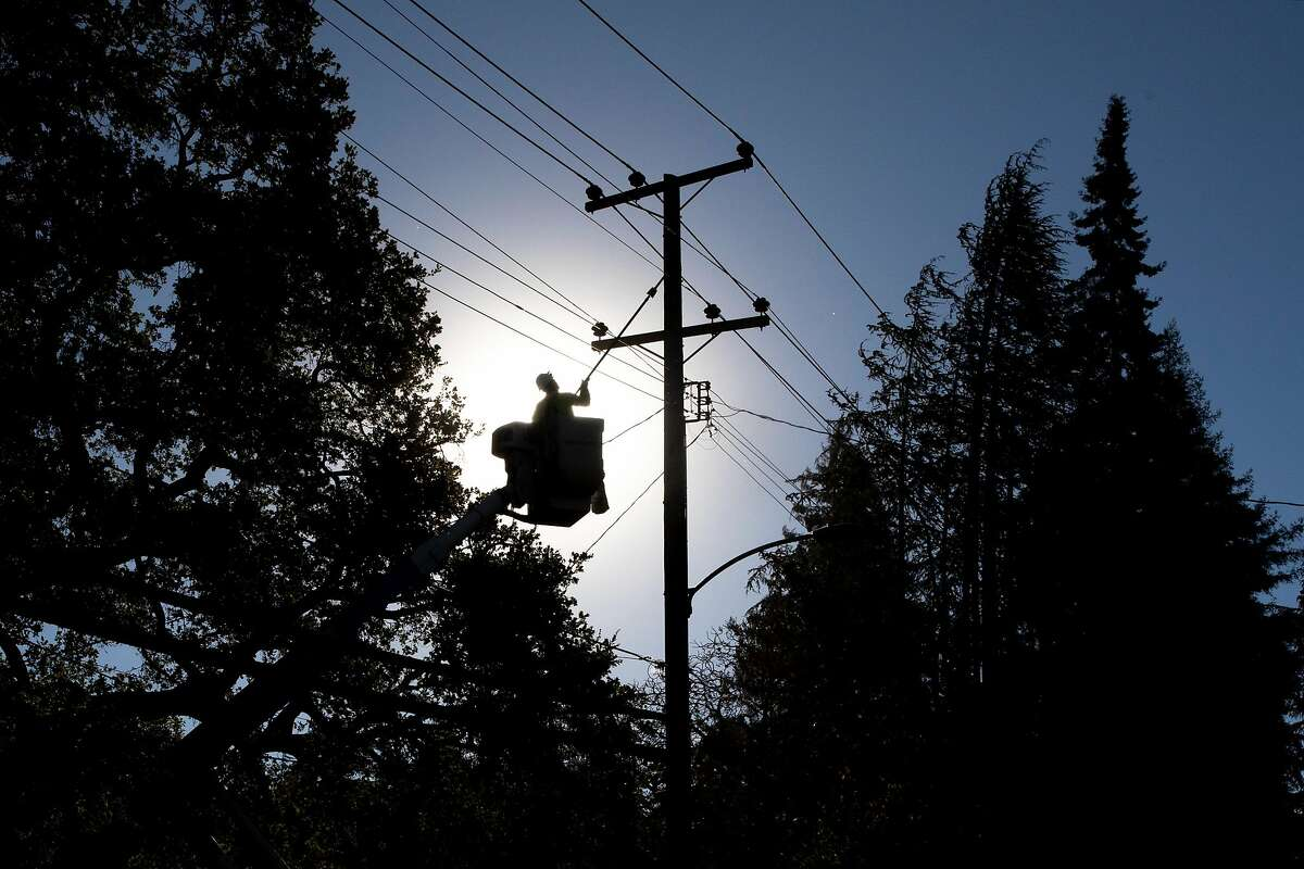 PG&E line inspector Kevin Ogans works to clear lines in October 2020. The company is intentionally shutting off power for the first time in January due to wildfire risks.