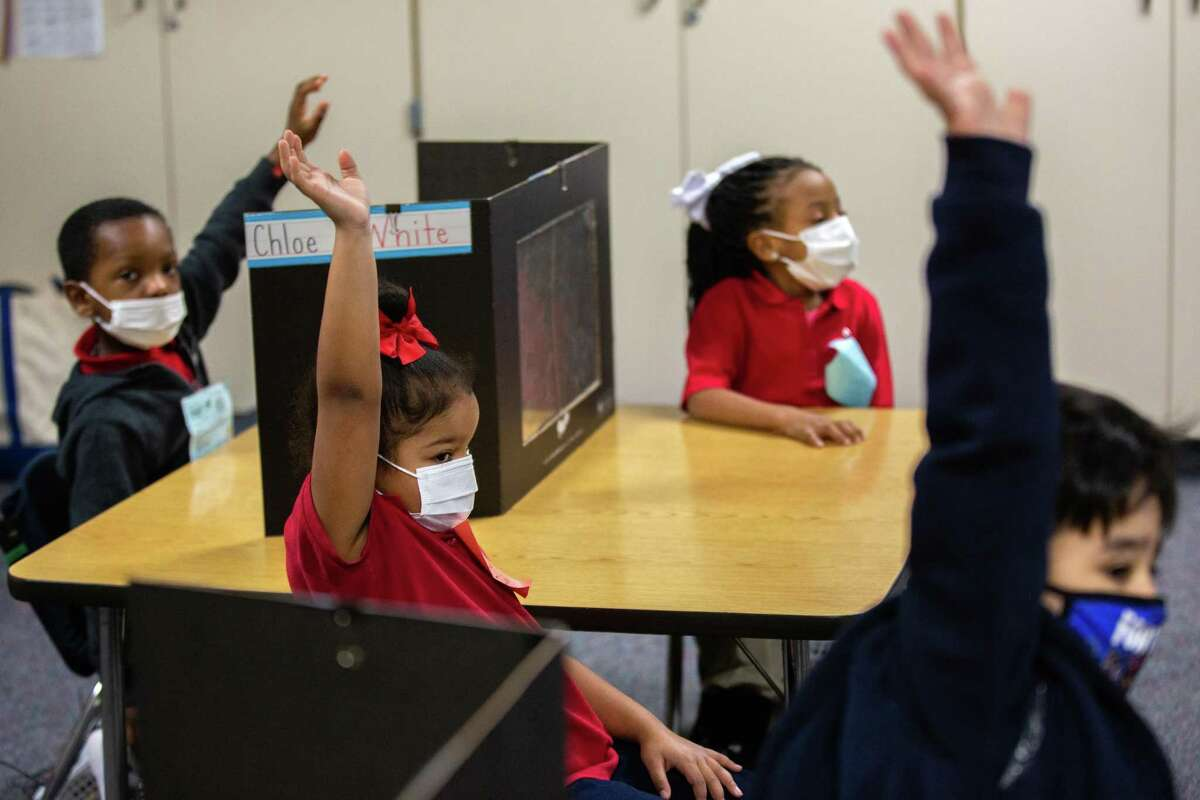 Best Elementary School kindergarten students raise their hands to participate in a class math exercise, Thursday, Dec. 3, 2020, in Houston.