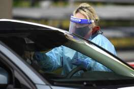 Laboratory technician Daphne Henri administers a drive-thru COVID-19 test outside The Doctors Office in the Cos Cob section of Greenwich, Conn. Tuesday, Nov. 17, 2020. The Doctors Office offers drive-thru COVID-19 nasal PCR tests during normal business hours.