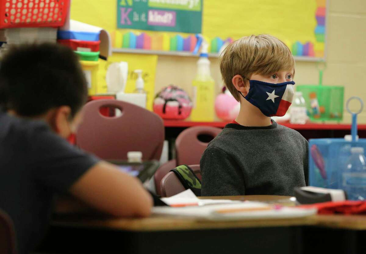 Third-grader Logan Sapp (right) wears a Texas flag-inspired mask in class on Thursday, Dec. 3, 2020. Students at Pearce Elementary at Southside ISD attend a combination of online and in-person class learning. According to Southside ISD Director of PR and Community Randy Escamilla, about half of the elementary school are currently in school and the other half are online as a result of the Coronavirus pandemic.