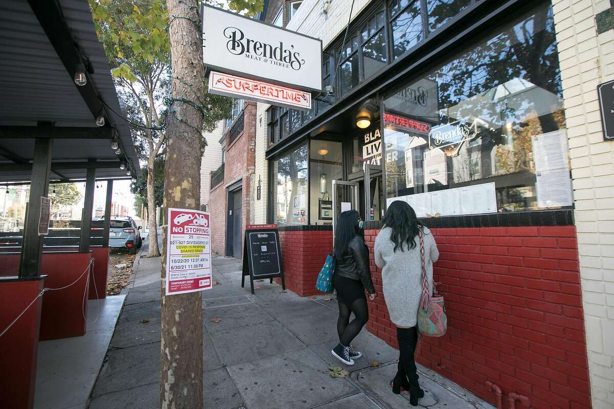 In this file photo customers look at a menu outside Brenda's Meat and Three on Divisadero Street in San Francisco. Like many other restaurants, Brenda's has been severely affected by the COVID-19 coronavirus pandemic.