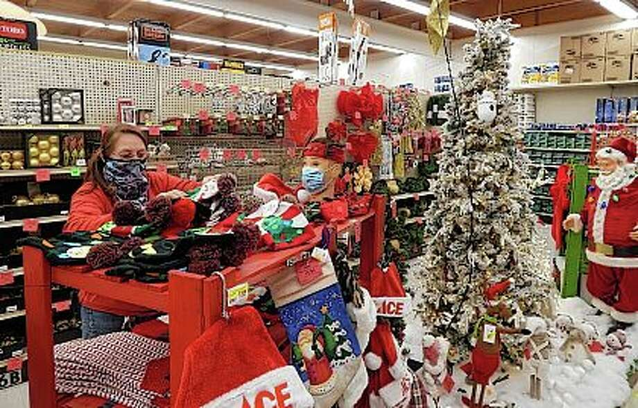 Ace Hardware manager Mickey Bourne straightens a display of Christmas stockings on Thursday at the store on West Morton Avenue. The store's stock of Christmas decorations has been hard hit as people who are spending more time at home amid the pandemic decide to decorate more than in past years. Photo: Angela Bauer   Journal-Courier