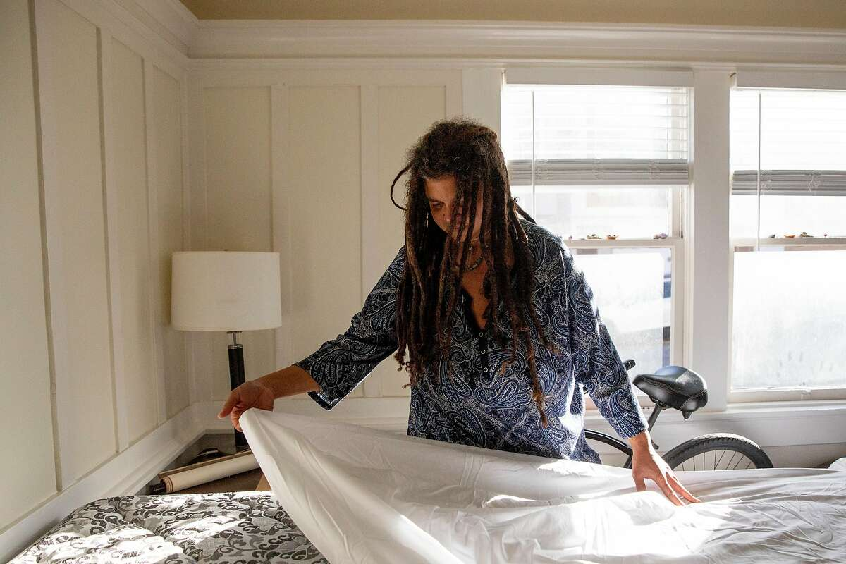 Shawn Landrum-Teppish puts sheets and bedding on her bed as she unpacks while moving into her own apartment in San Francisco, Calif. Tuesday, December 1, 2020. Landrum-Teppish, who has been living in a city-funded hotel room for the past few months, moved into a new housing unit on December 2. This is the first time Landrum-Teppish has had permanent housing in ten years.
