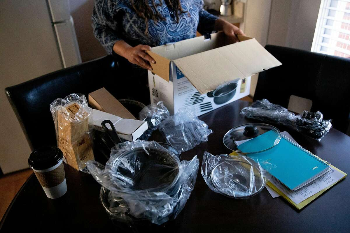 Shawn Landrum-Teppish unpacks a full kitchenware set while moving into her own apartment in San Francisco, Calif. Tuesday, December 1, 2020. Landrum-Teppish, who has been living in a city-funded hotel room for the past few months, moved into a new housing unit on December 1. This is the first time Landrum-Teppish has had permanent housing in ten years.