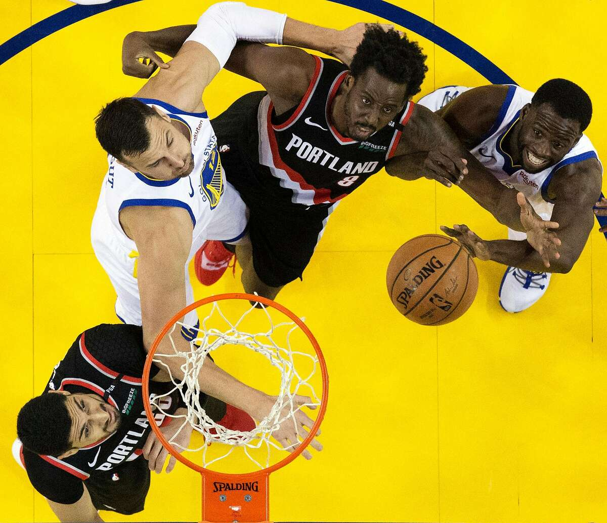 Andrew Bogut (12) and Draymond Green (23) battle Al-Farouq Aminu (8) and Enes Kanter (00) for a rebound in the first half as the Golden State Warriors played the Portland Trailblazers in Game 1 of the Western Conference Finals at Oracle Arena in Oakland, Calif., on Tuesday, May 14, 2019.
