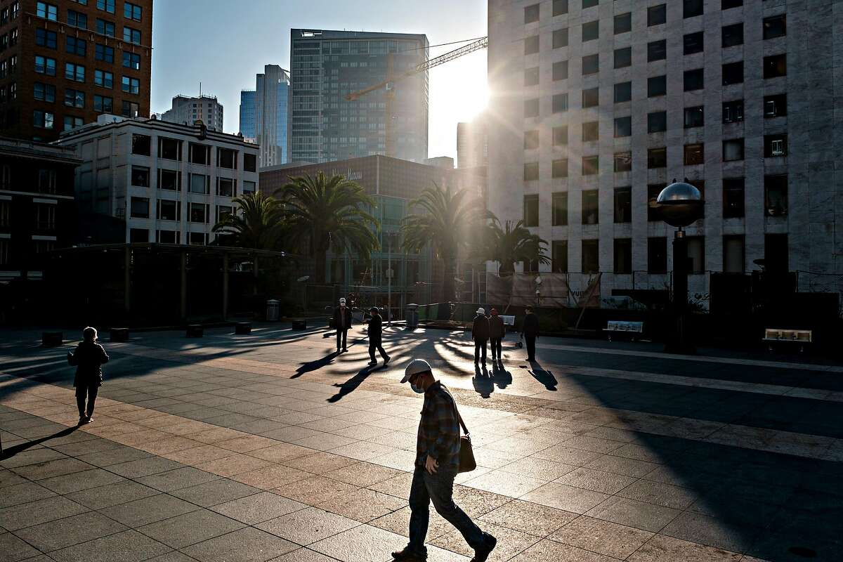 People are seen in the early morning light in Union Square in San Francisco on Friday. San Francisco is among the counties issuing stay-home orders again to curb a surge in the coronavirus.