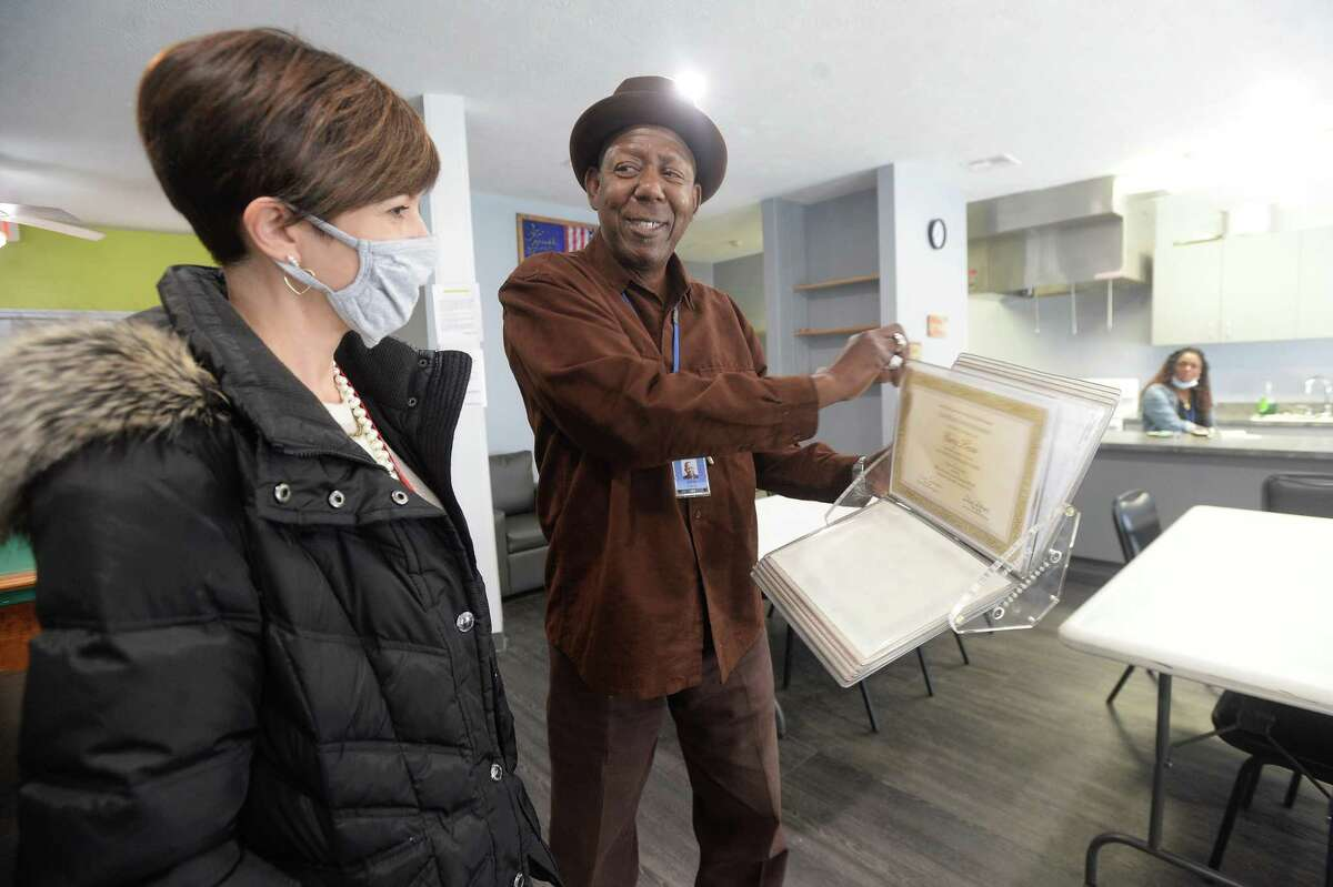 Spindletop Center's Heather Champion talks with Director Garry Lewis as he shows her his binder full of certifications and recognition as she stops to view The Hope Center, which reopened Monday after remaining closed and under repair since flooding during Tropical Depression Imelda. Photo taken Tuesday, December 1, 2020 Kim Brent/The Enterprise